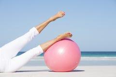 Женщина протягивая тренировки ног на пляже Стоковое Фото
