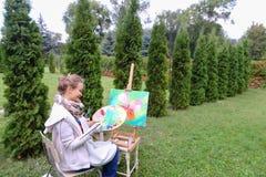 Женщина профессионального художника пишет изображение сидя на мольберте с b Стоковая Фотография RF