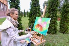 Женщина профессионального художника пишет изображение сидя на мольберте с b Стоковые Изображения RF