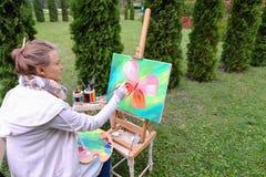 Женщина профессионального художника пишет изображение сидя на мольберте с b Стоковое фото RF