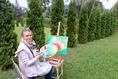 Женщина профессионального художника пишет изображение сидя на мольберте с b Стоковые Изображения