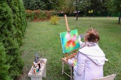 Женщина профессионального художника пишет изображение сидя на мольберте с b Стоковое Фото