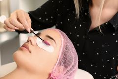 Женщина проходя процедуру по расширений ресницы в салоне стоковые фотографии rf
