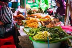Женщина продавая еду на местном продовольственном рынке, Индонезии Стоковое Изображение