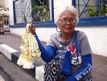 Женщина продает гирлянды цветков sampaguita Стоковая Фотография RF