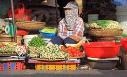 Женщина продает овощи на уличном рынке в оттенке стоковое изображение