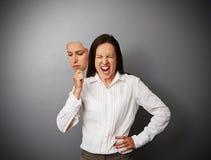 Женщина пряча ее гнев за маской Стоковое Фото