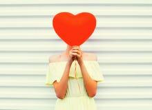 Женщина прячет головную красную форму сердца воздушного шара над белизной Стоковые Изображения