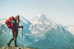 Женщина путешественника взбираясь к саммиту горы с рюкзаком Стоковые Фото