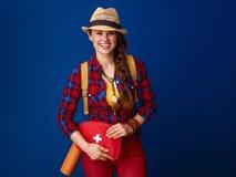 Женщина путешественника изолированная на голубой предпосылке с бортовой аптечкой Стоковые Изображения