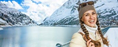 Женщина путешественника перед ландшафтом горы зимы с озером Стоковая Фотография