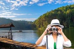 Женщина путешественника принимает фото и распологающ на террасу на курорте дальше насладитесь и ослабьтесь с внешней природой стоковое изображение rf