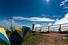 Женщина путешественника принимает фото на зоне горы близко располагаясь лагерем Стоковое Изображение RF
