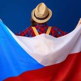 Женщина путешественника против голубого флага удерживания предпосылки чеха Стоковое Изображение RF