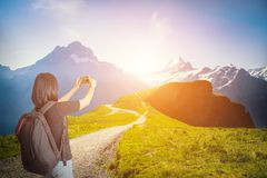 Женщина путешественника с альпинизмом рюкзака и принимает фото  Стоковая Фотография RF