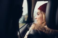 Женщина путешествуя автомобилем и смотря внешнее окно Стоковое фото RF