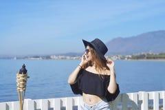 Женщина путешествуя говорить на телефоне, милая улыбка девушки, на предпосылке моря/океана Концепция соединения и communicati Стоковые Изображения