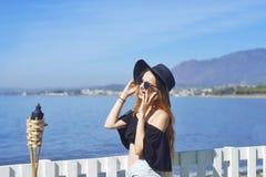 Женщина путешествуя говорить на телефоне, милая улыбка девушки, на предпосылке моря/океана Принципиальная схема соединения Стоковая Фотография