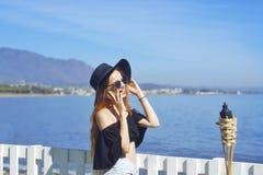Женщина путешествуя говорить на телефоне, милая улыбка девушки, на предпосылке моря/океана Принципиальная схема соединения Стоковые Изображения