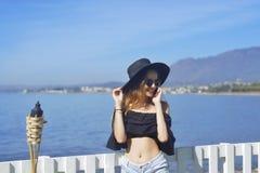 Женщина путешествуя говорить на телефоне, милая улыбка девушки, на предпосылке моря/океана Принципиальная схема соединения Стоковые Изображения RF