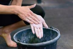 Женщина пылясь ее руки с мелом в спортзале стоковое фото