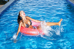 Женщина плавая в автомобильную камеру в бассейне и имея потеху Стоковые Фотографии RF