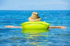 Женщина плавая на сплоток в тропическом океане Стоковое фото RF