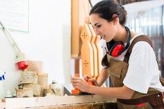 Женщина плотника работая с planer в ее мастерской стоковое фото