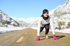Женщина работаемая в дороге ландшафта зимы стоковая фотография