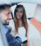 Женщина работает с привлекательной улыбкой в автомобиле Стоковые Фото