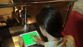 Женщина работает с таблеткой в руках с зеленым экраном, ключе chroma, пользуясь ключом сидя таблица сток-видео
