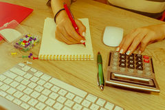 Женщина работая в офисе, сидя на столе, используя компьютер Женщина руководителя бизнеса на рабочем месте Налог коммерсантки расч Стоковое фото RF