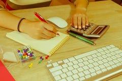 Женщина работая в офисе, сидя на столе, используя компьютер Женщина руководителя бизнеса на рабочем месте Налог коммерсантки расч Стоковые Фотографии RF