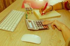 Женщина работая в офисе, сидя на столе, используя компьютер Женщина руководителя бизнеса на рабочем месте Налог коммерсантки расч Стоковые Изображения