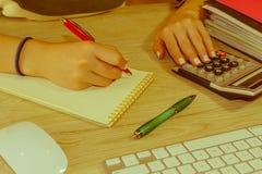 Женщина работая в офисе, сидя на столе, используя компьютер Женщина руководителя бизнеса на рабочем месте Налог коммерсантки расч Стоковое Изображение RF