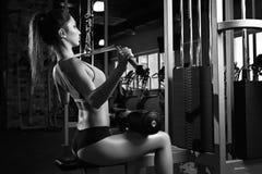 Женщина работая назад на машине в спортзале стоковые фотографии rf