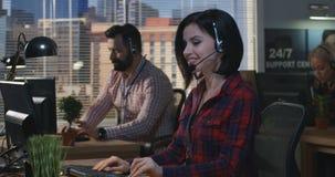 Женщина работая на его столе в центре телефонного обслуживания