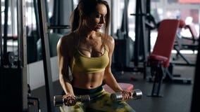 Женщина работая на ее бицепсе в спортзале Стоковое Фото