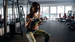 Женщина работая на ее бицепсе в спортзале Стоковые Фотографии RF