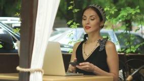 Женщина работая на компьтер-книжке в кафе и отвечая звонку, селективному фокусу сток-видео