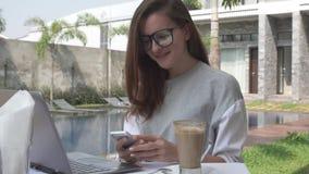 Женщина работая на компьтер-книжке и smartphone взятия около бассейна на тропической роскошной вилле Женская работа на компьютере видеоматериал