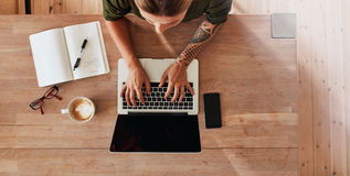 Женщина работая на компьтер-книжке на кафе Стоковые Изображения