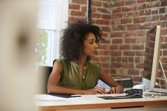 Женщина работая на компьютере в современном офисе Стоковые Фотографии RF
