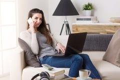 Женщина работая на компьютере и говоря на телефоне Стоковое фото RF