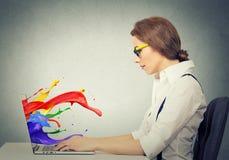 Женщина работая на компьютере красочном брызгает приходить из экрана стоковые фото