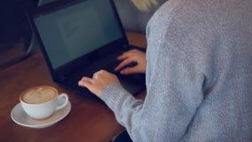Женщина работая на ноутбуке и кофе напитка акции видеоматериалы