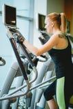 Женщина работая на перекрестных машинах тренера Стоковое Фото