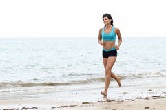 Женщина работая на пляже Стоковое Изображение