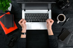 Женщина работая на таблице офиса Взгляд сверху человеческих рук, клавиатуры компьтер-книжки, чашки кофе, smartphone, тетради и a Стоковое Изображение