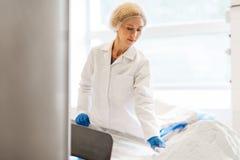 Женщина работая на транспортере фабрики мороженого Стоковое фото RF